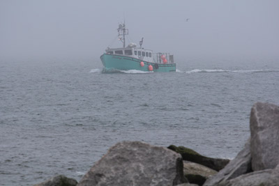 The incoming tide brings with it fog, but also means lobster boats can return to the harbor.
