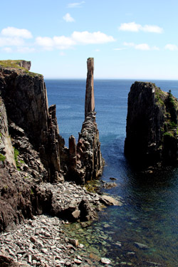 A dramatic spire rises from the waters of Spillar's Cove